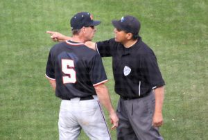 An umpire directs Oregon State head coach Pat Casey  to return to the dugout. (Shotgun Spratling)
