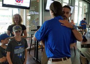 Chris Pollard hugs a player as his wife Stephanie looks on with a smile (Aaron Fitt)