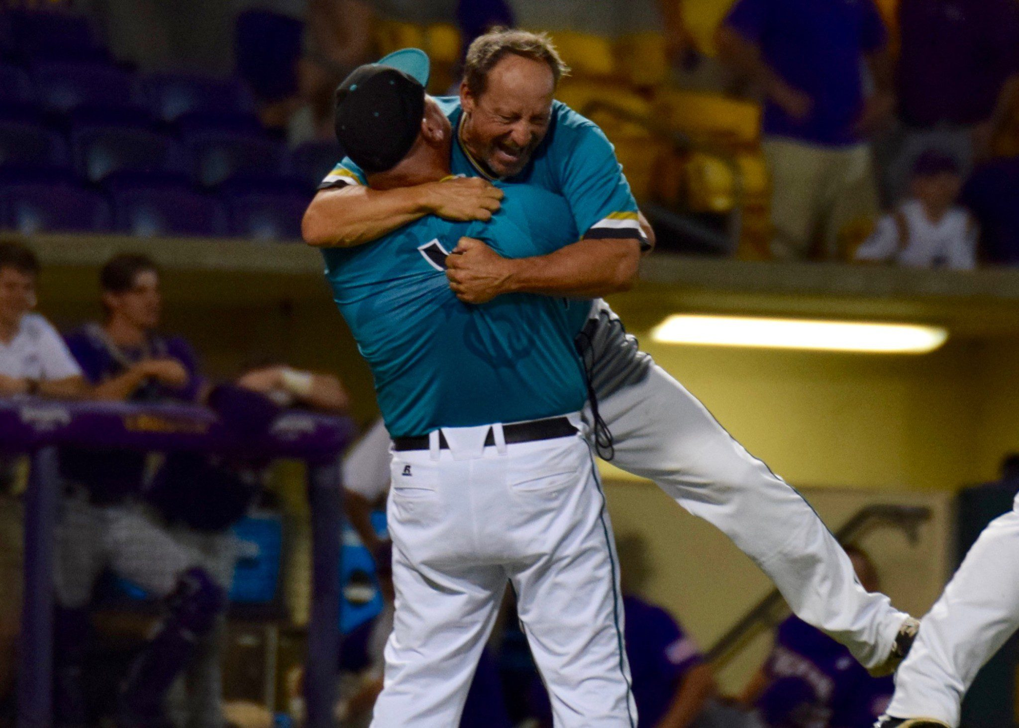 Coastal Carolina volunteer assistant Matt Schilling lifts head coach Gary Gilmore into the air after clinching the program's first trip to Omaha (Aaron Fitt)