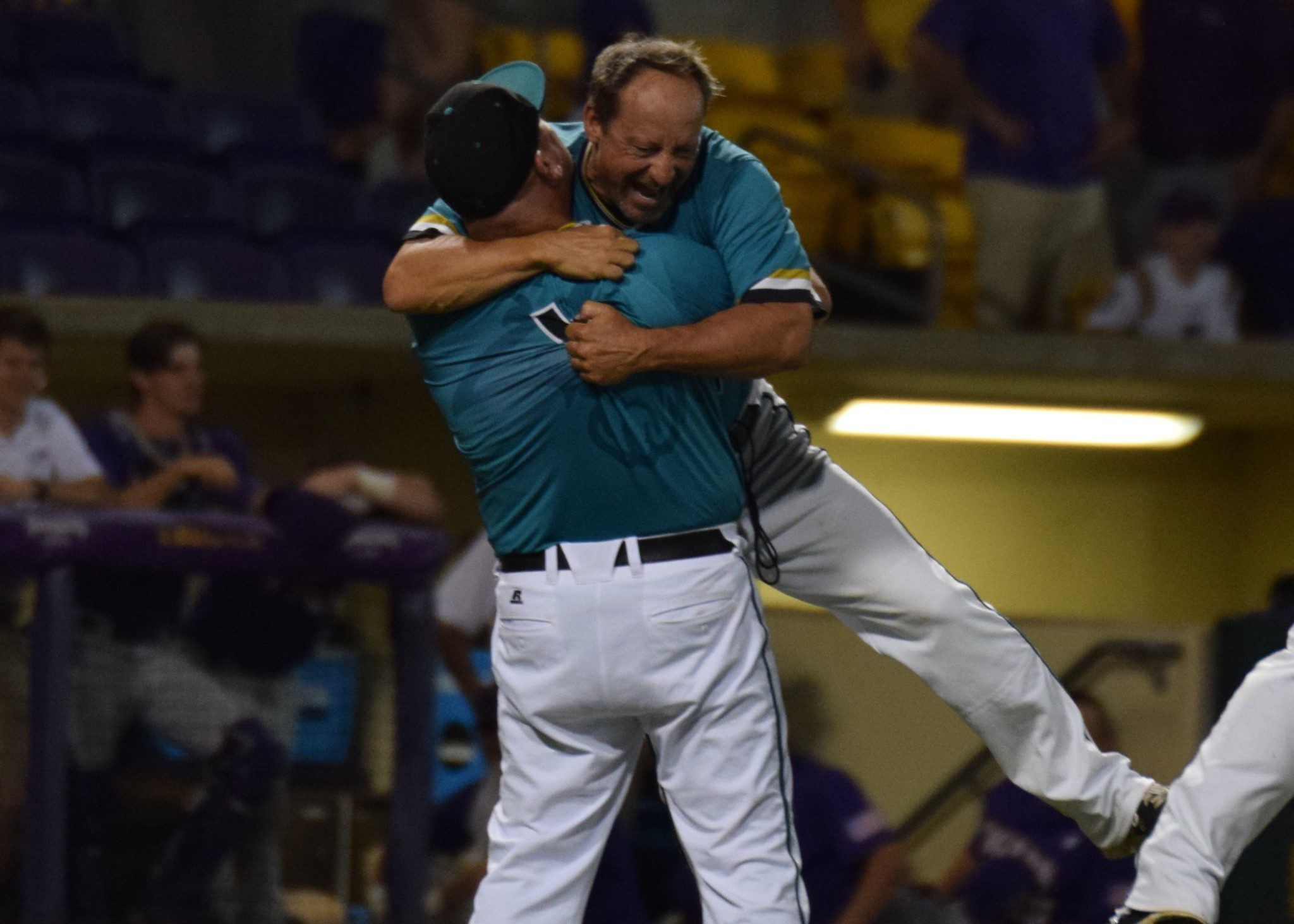 Coastal Carolina volunteer assistant Matt Schilling lifts up head coach Gary Gilmore after the Chants clinched their first trip to Omaha (Aaron Fitt)